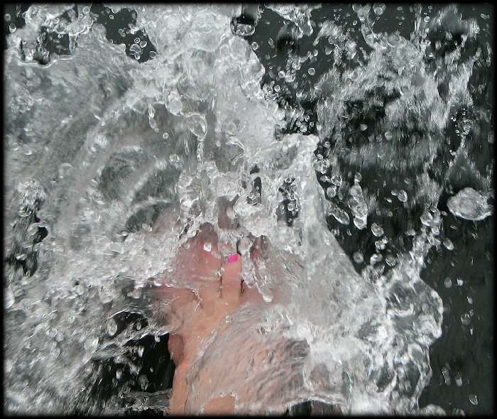 Jessica pushing her feet through the water at the front of the boat